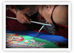 Monks from the Drepung Gomang Monastery in Tibet recreate a sand mandala.  A toddler ran through the mandala the day before and destroyed the monks' work.  The monks were not angry, but had  compassion for the toddler and quietly started over.